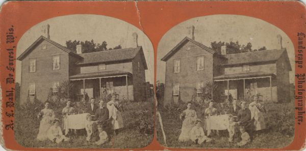 "A family poses for a portrait outdoors in front of their house. The eight individuals gather around a table on their front lawn for the photograph. Caption on back of stereograph reads, ""Mrs. Beret H. Stugaard and Familie[sic], Springdale, Wisconsin."""