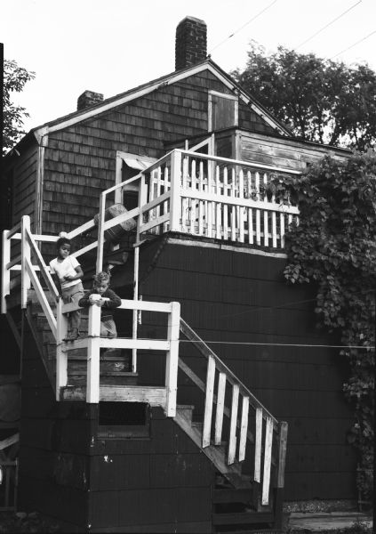 "Two children stand on an outdoor stairway of wood-shingle house. Caption on back of print reads, ""Back steps in 'Goosetown.' a section around Broadway and 9th Street, an old residential island surrounded by industrial plants and bare flats."""