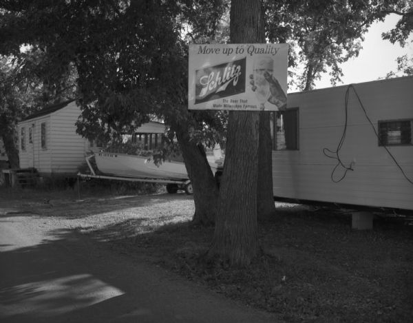 "A cottage and trailer house community along a river. A Schlitz beer advertising is nailed to a tree and reads, ""Move up to Quality / Schlitz / The Beer That Made Milwaukee Famous."""