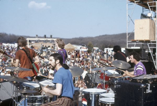 Side view of the Grateful Dead on stage, featuring Bob Weir, Mickey Hart, Phil Lesh, Jerry Garcia, and Bill Kreutzmann, play on stage at the Sound Storm Festival. In the background is a large crowd and tents.