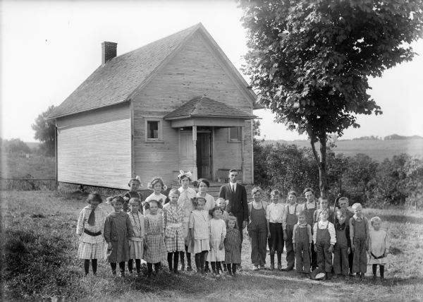 A group of children with their teacher pose on the lawn outside a one-room school building.