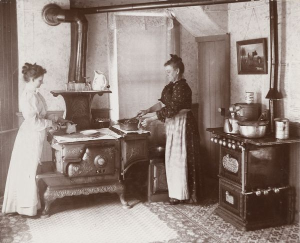 Interior of the kitchen at 12 North Broom Street, the residence of James and Mary Ellen Nevin, showing Mrs. Nevin and her sister cooking. James Nevin was the Wis. Superintendent of Fisheries and the Nevin Fish Hatchery is named for him.