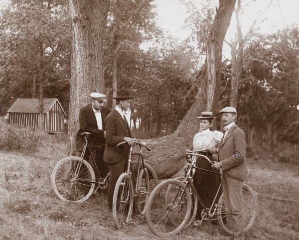 Mr. and Mrs. H. Schildhauer and Louis and Henry Harder stand near a large tree and rest from a bike ride on Mendota Drive.