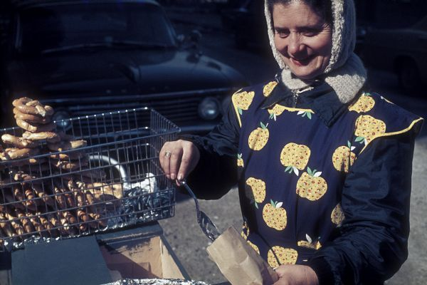 A woman street vendor, in an embroidered jacket, sells pretzels on the street near the construction site of the World Trade Center.