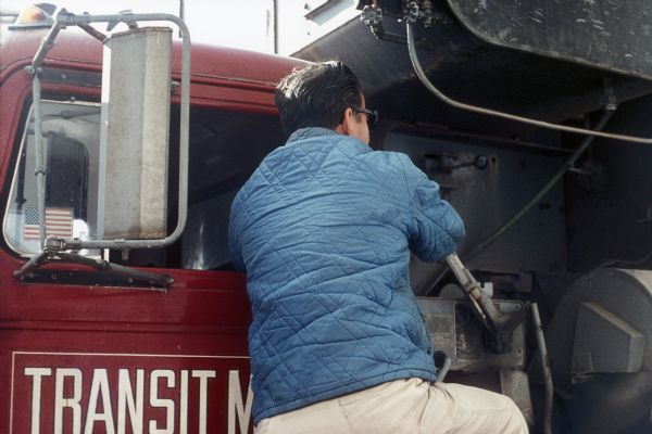 A man, with his back to the camera, operating a lever behind the cab of a large construction truck.