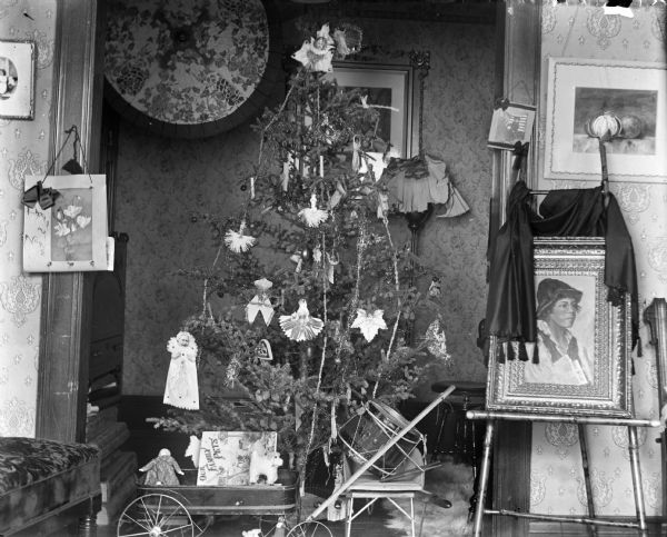 A decorated Christmas tree surrounded by toys, including a wagon, drum, and wheelbarrow. A painting is displayed on a stand nearby, and a painted umbrella is on the wall behind the tree.
