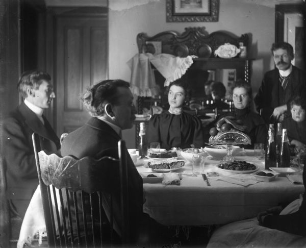 A group of family members sitting at a table laden with food for a New Year's dinner.