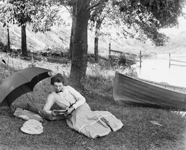 Woman lying in the grass reading near an umbrella along a shoreline. A boat is beached on the right, and in the background is a fence and hill.