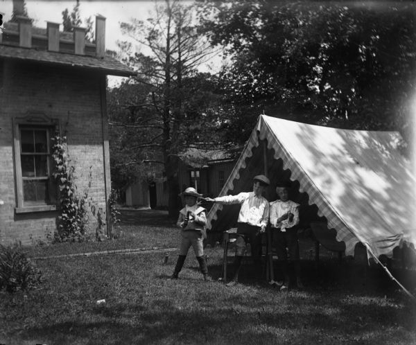 Three boys holding fireworks stand near a tent or open-sided awning in a backyard near a house.