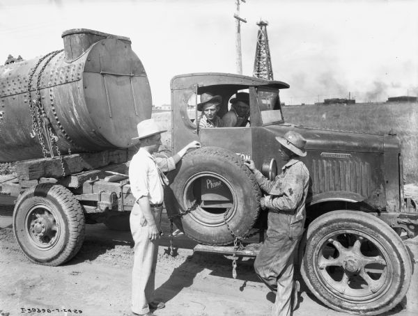 Men standing next to an International heavy-duty oil truck. Two delivery drivers from Barrington Transfer Company are in the cab of the truck. An oil well is in the far background.