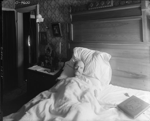 A man lays in bed, covered to his chin in bedding and propped up by pillows. Laying next to the man on the bed is a large bible and a rosary. The room is richly decorated with a large wooden headboard and wallpaper. Beside the man is a table with tablecloth on which sits a religious shrine. There is also a glass candle holder in the shape of a cross, what appears to be an ink well and pen, and another jar. Above the table are two religious paintings and a lamp with a card attached to the side of the glass shade. This man may have been an employee at International Harvester's Osborne Works in Auburn, New York.