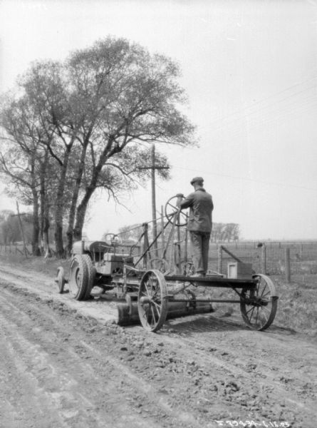 Three-quarter view from left rear of a man driving an industrial tractor pulling road construction equipment.