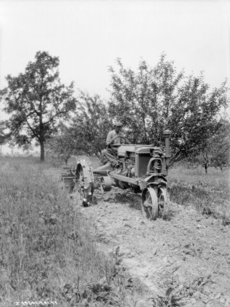 A man is driving a Farmall tractor pulling a plow. Trees are in the background.