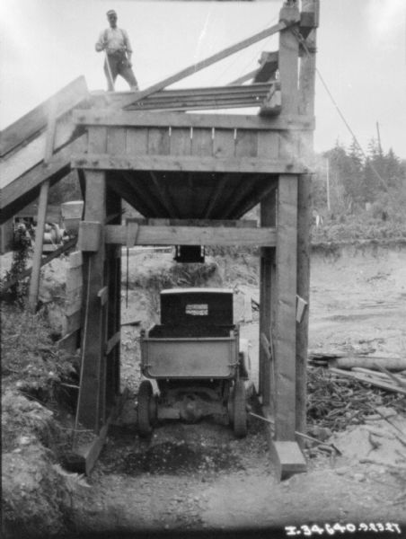View of back of delivery truck underneath a wooden structure with a hopper to fill the back of the truck bed. A man is standing on top of the structure.