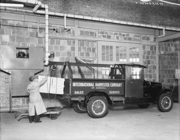 View across shop floor towards a man loading a crate onto an International Harvester Company of America sales and service truck. The man is using a Ford Triblock 1 ton block and tackle mounted on the truck. There are large doors or windows in the brick wall behind the truck.
