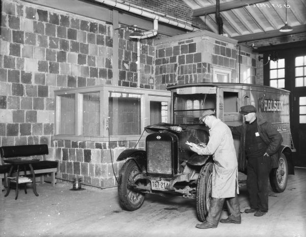 "Man checking engine of a truck in a repair shop. The sign on the side of the truck reads: ""Holsum Baking Co."" The license plate on the front of the truck reads: ""Ohio 1929."" Against the wall on the left is a bench, table, and spittoon."