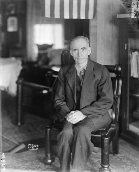 Portrait of a man wearing a suit sitting in a chair.