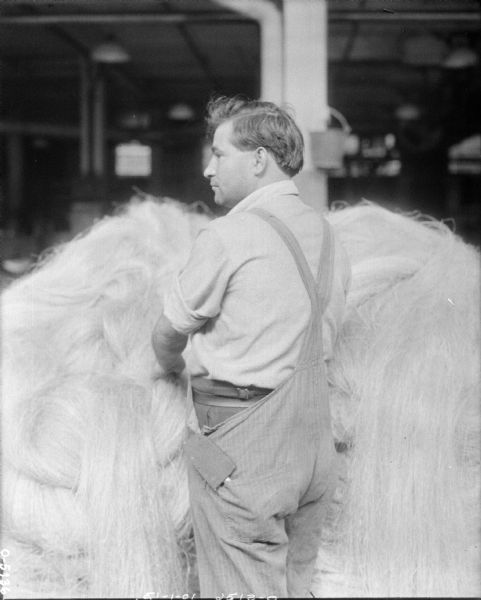 A man is standing in front of a large pile of manila hemp fiber. The fiber was used to create twine. The man is wearing overalls over his clothing and has his shirt sleeves rolled up. He is likely an employee of the International Harvester Osbourne Works in Auburn, New York.