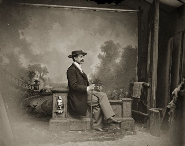 Charles J. Van Schaick sitting on a stone balustrade in front of a painted background, ca. 1882–1885. The photograph was probably taken by one of his assistants, Louis Sander, A.R. Cottrell, or S. Wohl.