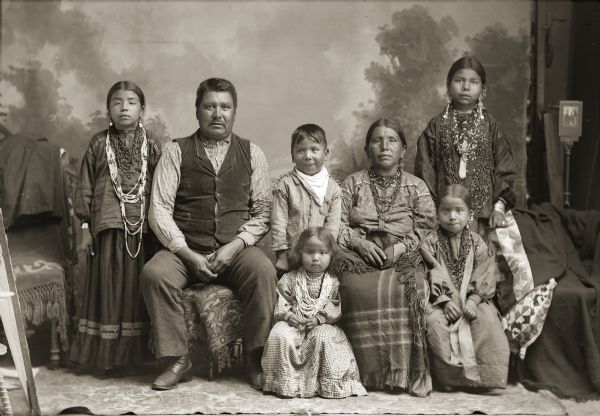 Full-length studio portrait of a Ho-Chunk family, including a man, woman, four girls, and a boy posing in front of a painted backdrop. The woman and older girls are wearing degrees of regalia, and the remaining individuals are wearing contemporary dress. The Whitebear family was referred to in the census rolls with the last name of White but they used the name Whitebear. From left to right are Ella Whitebear (MauNaPayWinKah), father Jim Whitebear (HoonchSkaKah), Dan Whitebear (HeNukKah), mother Kate Whitebear (MawChePauSayWinKah), and Daisy Whitebear (WeHunKah). Lucy Whitebear (HoDaHooKah) sits in front of Dan, and Viola Whitebear (UkSeUkKah) is sitting in front of Daisy.