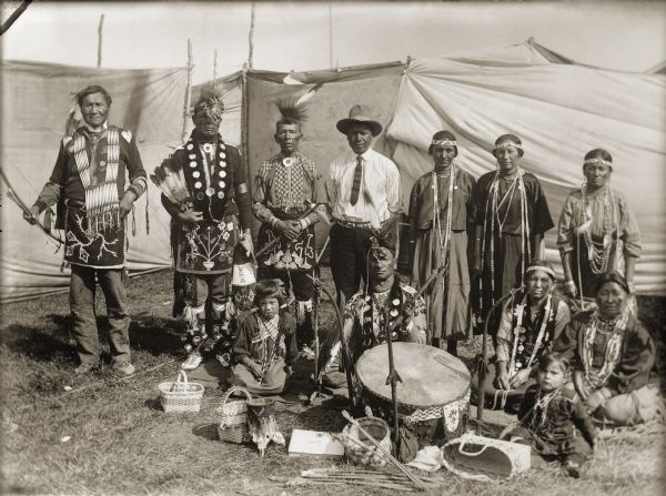 Ho-Chunk performers gathered behind a drum and Winnebago baskets at the 1908 Homecoming. Standing from the left are Jim Swallow (MaPaZoeRayKeKah), William Massey (ChawRoCooChayKah), George Eagle (WaNaKeeScotchKah), Benjamin Thundercloud (NySaGaShiskKah), and Flora Thundercloud Funmaker Bearheart (WaNekChaWinKah). The woman standing on the far right is Susie Lena Pettibone Johnson (ChoNukKaWinKah), and the woman seated to the left is Addie Littlesoldier Lewis Thunder (KzunchJeKahRayWinKah). Thomas Thunder (HoonkHaGaKah) is seated beside her behind the drum. Remaining names are unknown.