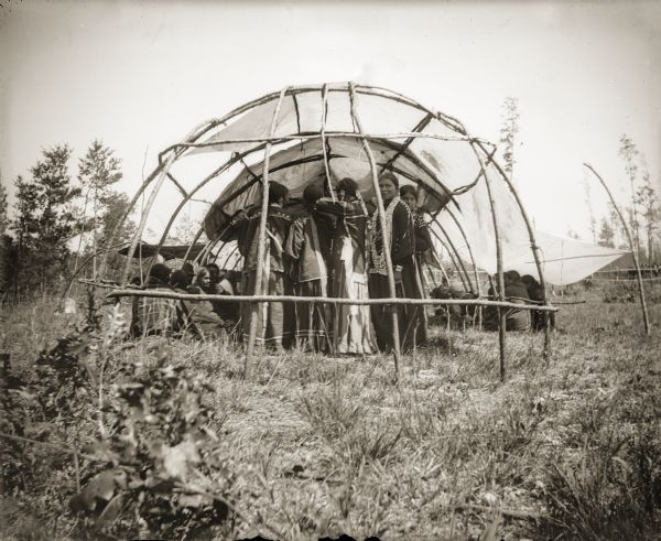A group of Ho-Chunk people standing in the rear of a Buffalo Dance Lodge. The Buffalo Dance would take place in the spring, when the grass was long enough to tie in a knot.