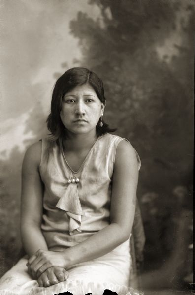 Three-quarter length studio portrait of a young Ho-Chunk woman in short hair posed sitting and wearing modern dress in front of a painted backdrop. She is wearing a dress and earrings. Identified as Lavina Davis (UkSuUkKah), reportedly the first Ho-Chunk woman to wear slacks.