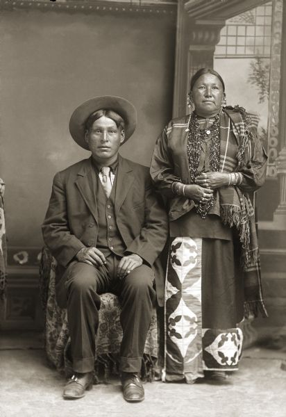 Studio portrait of George Monegar (EwaOnaGinKah) and Fannie Stacy Lincoln Monegar (LeBaWinKah) posing standing in front of a painted backdrop. He is wearing a suit jacket, vest, tie, and hat, and she is wearing beads, a long embroidered skirt, and wool shawl. Fannie Stacy Lincoln Monegar is the mother of Frank Lincoln according to the notes of Jackson County Historical Society, Wisconsin.