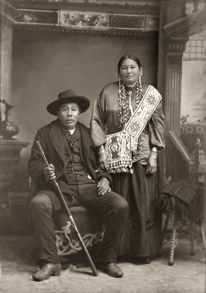 Full-length studio portrait of a Ho-Chunk man, George Greengrass and his wife in front of a painted backdrop. George Greengrass (WauKeCooPeRayHeKah) and Emma Lookingglass Greengrass (ChayHeHooNooKah). Emma is standing and wearing a bandolier with an offset top strap which was common to Ho-Chunk bandolier bags. He is the grandfather of LaVern Carriman. He is sitting holding a rifle and is wearing a hat, suit jacket, vest with watch fob, scarf, and trousers.