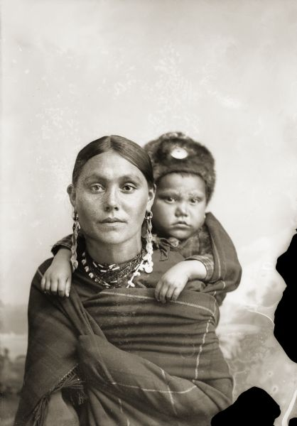 Quarter-length studio portrait of a woman in Ho-Chunk regalia wrapped in a blanket, with a child on her back. The child is wearing a fur hat, and they are posing sitting in front of a painted backdrop. Clara Kingsley (Big) Blackhawk (KeesKawWinKah) carries her son Andrew John (Big) Blackhawk (WaConChaHoNoKah) on her back. Using a shawl as a back sling was a common way to carry infants in this period.