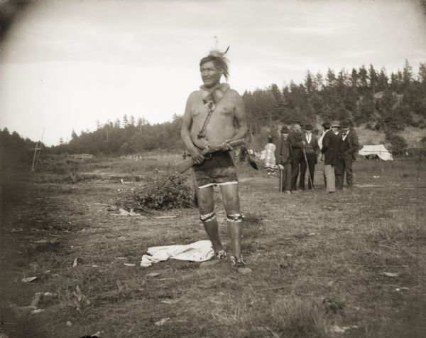 "Ho-Chunk man posing standing in a open field holding a flintlock gun. He is wearing garters, moccasins, a breech cloth, necklace, and feathers in his hair. In the background is a group of European American men standing together, and in the far background is a tree-covered hill. He is identified as John Greencloud ""Green Thunder"" (WauKonChawChoKah), at Frog Place in the Morrison Creek Bottoms at Brown Eagle place. John served in the Civil War as a scout for the U.S. Army with the Comanches."
