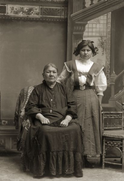 Full-length atudio portrait in front of a painted backdrop of Lucy Goodvillage Blowsnake (NauNawZokeAWinKah) sitting beside her granddaughter Nina Thunder Decorah Green (AhHooGeNaWinKah), who is standing on the right. Lucy is wearing a Christian cross around her neck.
