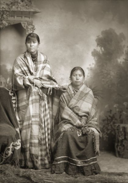Full-length studio portrait in front of a painted backdrop of Annie (Katie) W. Blowsnake (MaHeHaNaSheWinKah) standing next to a woman identified as her mother. Both women are wearing Racine Woolen Mills shawls.