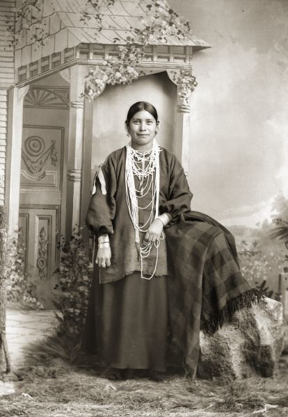 Full-length studio portrait of a Ho-Chunk woman, Mary Alice Johnson Decorra Brown (ENooKah), posing standing in front of a painted backdrop. SHe is wearing beads, earrings, and file bracelets. Probably the sister of John Johnson.