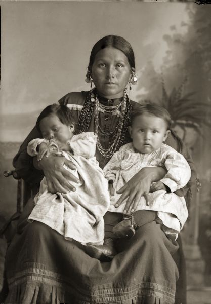 Studio portrait of Mountain Wolf Woman, also known as Stella Blowsnake Whitepine Stacy (HayAhChoWinKah), sitting and holding her two daughters, Josephine Whitepine Mike (AhHooGeNaWinKah), left, and Lena Whitepine Shegonee (HaCheDayWinKah). <i>Mountain Wolf Woman</i> is also the title of a book written about her by Nancy Lurie.