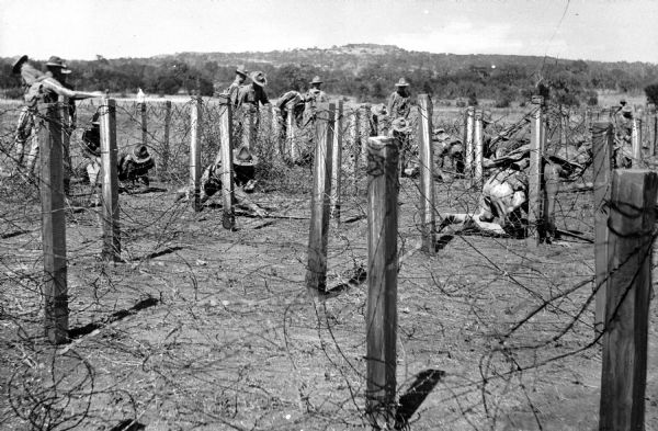 A view of soldiers maneuvering under barbed wire at Camp Travis, named in 1917.