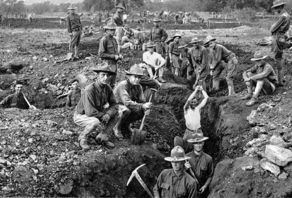 A view of soldiers digging trenches, some holding shovels or pickaxes, at Camp Travis, named in 1917.