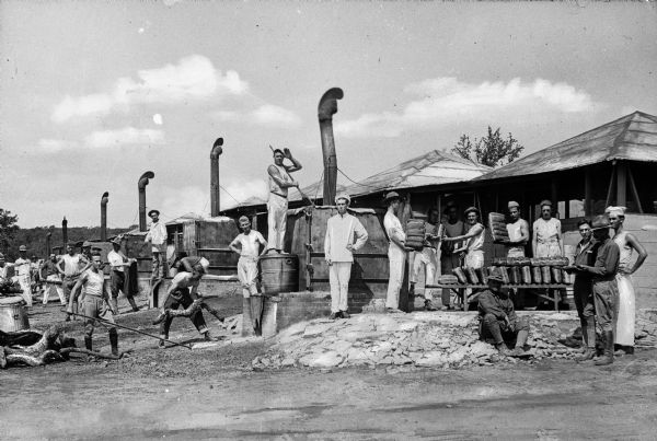 A view of men baking bread in a number of outdoor ovens at Camp Travis, named in 1917.  On the right, men stand by a table with many loaves of bread, and men on the left work with the ovens.