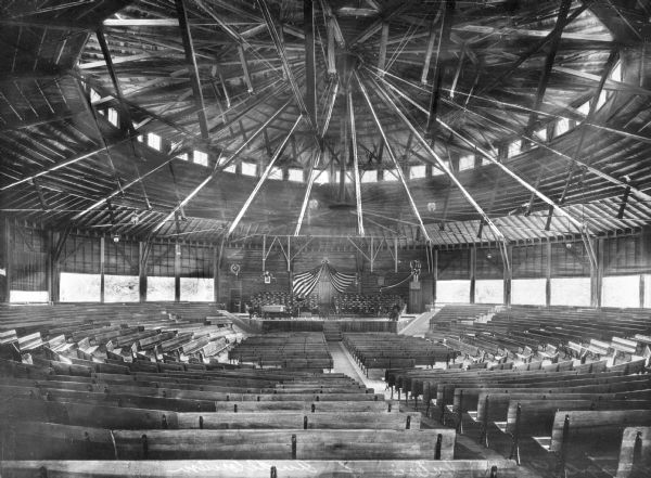 Interior of an auditorium.  Wooden benches surround a platform where two United States flags are visible.  On the ceiling, wooden beams make up the circular form of the building.