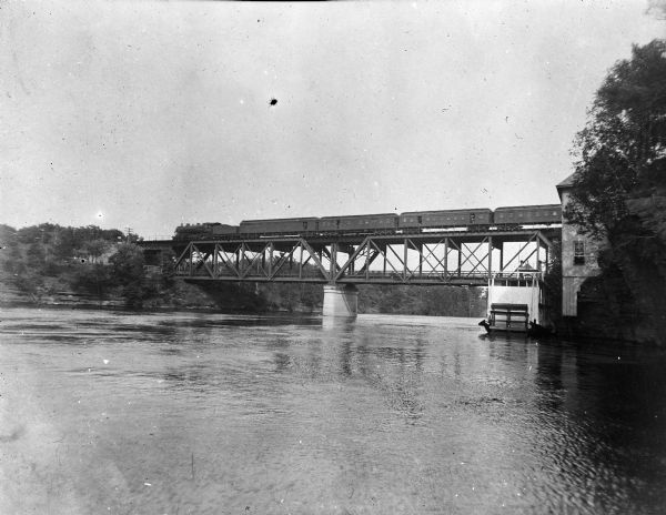 A Chicago, Minneapolis, and St. Paul train crosses a bridge over the Wisconsin River.