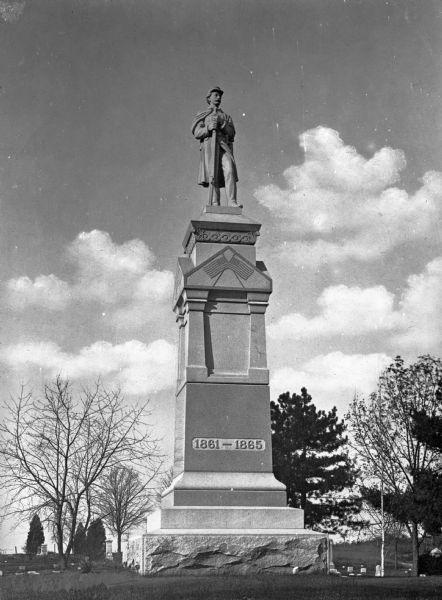 View of the Soldier's Monument, erected in 1898 at Evergreen Cemetery, sponsored by the Grand Army of the Republic.  The monument, featuring a soldier and two United States flags, memorializes the soldiers of the Civil War.  Headstones can be seen behind the monument.