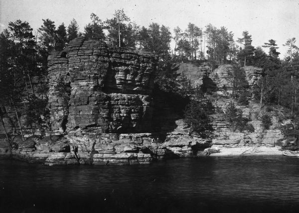 A man and woman sit along the shoreline of the Wisconsin River near Chimney Rock.