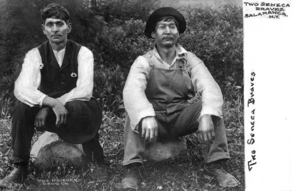 "Two Seneca Native American men posed sitting on rocks. Text on the photograph reads, ""Two Seneca Braves"" and ""The Krieger Drug Co."""