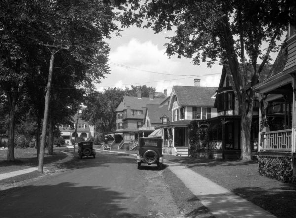 A view of a street, with houses on the right side and tress lining the left. Utility lines run the length of the street, and two automobiles are parked at the curb, one on each side of the street.