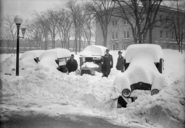Winter scene with three men standing beside parked cars that have been buried by snowfall and snowplow on Fourth Avenue, Baraboo, Wisconsin. The Sauk County Courthouse is on the right; commercial buildings along Oak Street may be seen in the background. A sign on a lamppost identifies Highway 33 West.