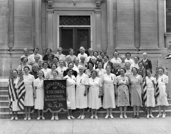 "A group of women stand on the steps of the Sauk County Courthouse. A banner identifies them as the Department of Wisconsin, National Daughters of the G.A.R. (Grand Army of the Republic).  The organization was founded in 1907; its members were female ""direct lineal descendants"" of Civil War (Union) veterans. The group disbanded in the late 1970's."