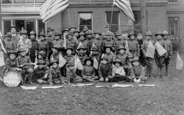 "Group portrait of a Boy Scout band in front of a large brick building, possibly the old Baraboo High School. The bass drum head reads ""Boy Scout Band"" and the boys hold flags and instruments."