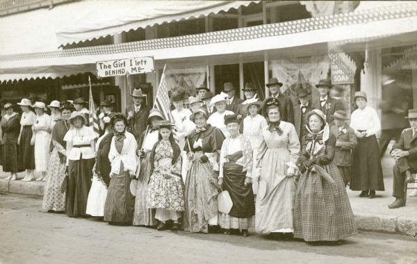 "Photographic postcard of a group of men and women dressed in clothing of the mid-nineteenth century pose at the side of a Baraboo Street. Most of the women are holding fans. Two women hold American flags; a man in the background holds a sign saying ""The Girl I left [sic] Behind Me."" Several women on the sidewalk at left are wearing clothing from the time the photograph was taken. A long patriotic banner has been hung above the sidewalk. There are large awnings on the buildings behind the group."