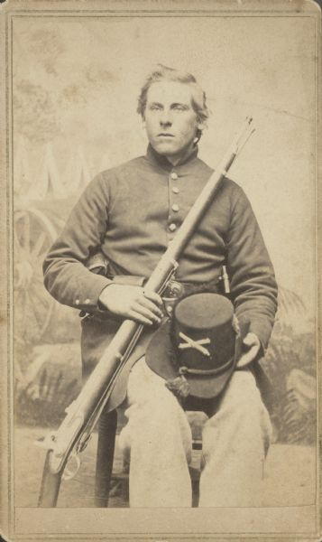 Seated carte-de-visite portrait in front of a painted backdrop of John Crossman, Company C, 1st Wisconsin Heavy Artillery, sitting with a musket across his chest and his hat on his lap.