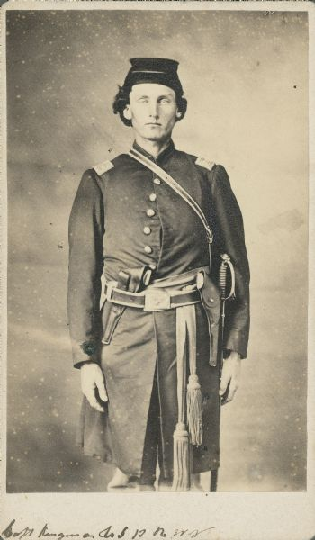 Three-quarter-length carte-de-visite portrait of Captain Newton H. Kingman, Company I, 13th Wisconsin Infantry, wearing full uniform with sidearm and sword on right side.